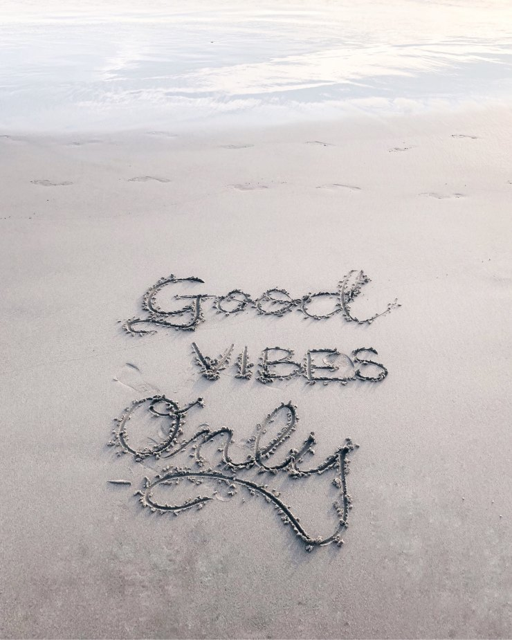 """""""Good vibes only"""" written in the sand"""