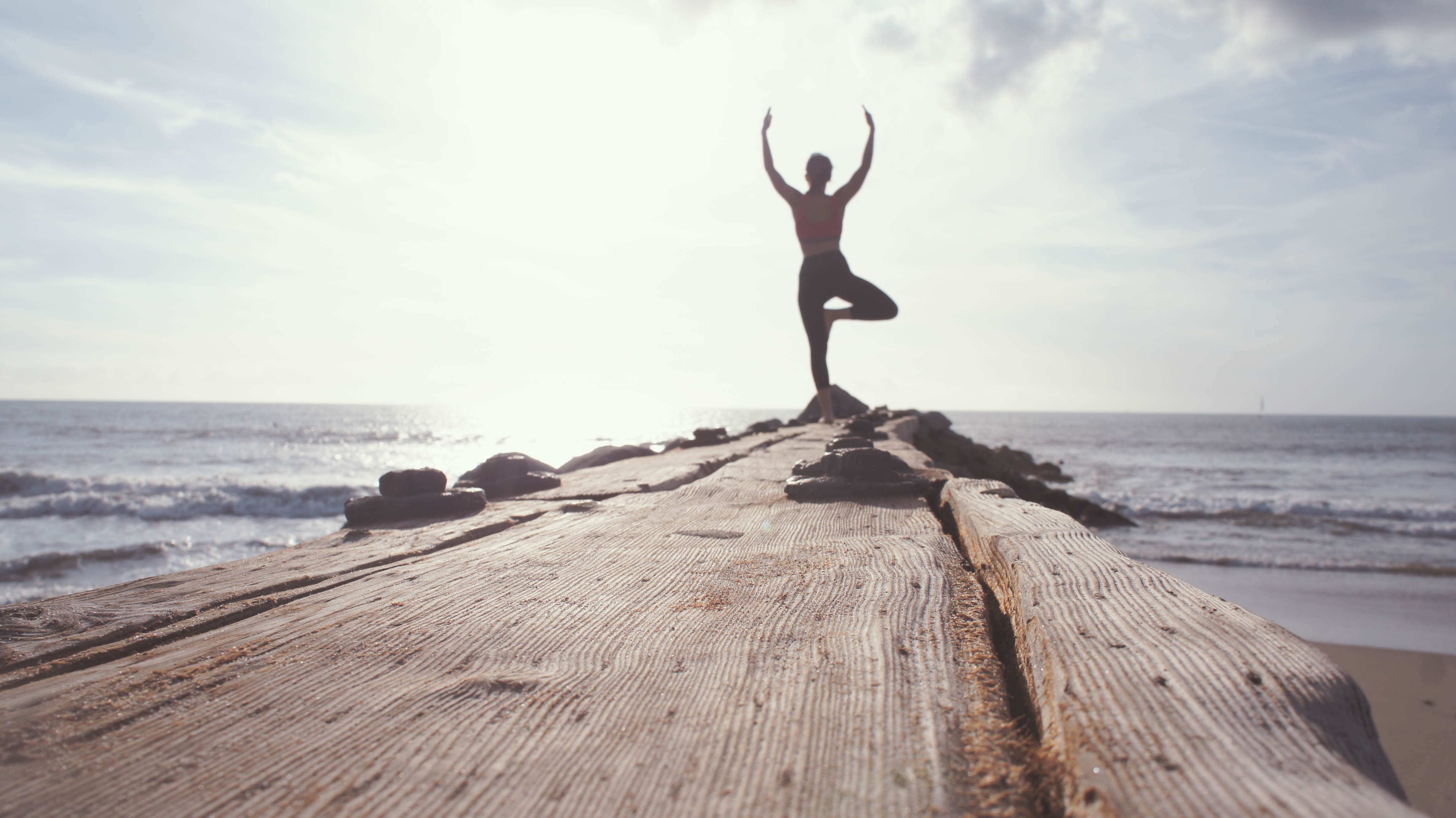 Woman practising Yoga stand at the seashore.