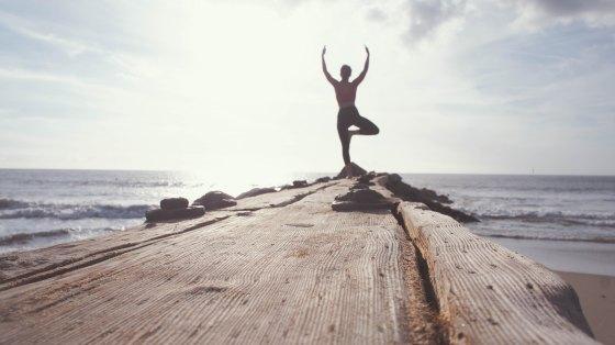 Woman practising Yoga stand at the seashore.