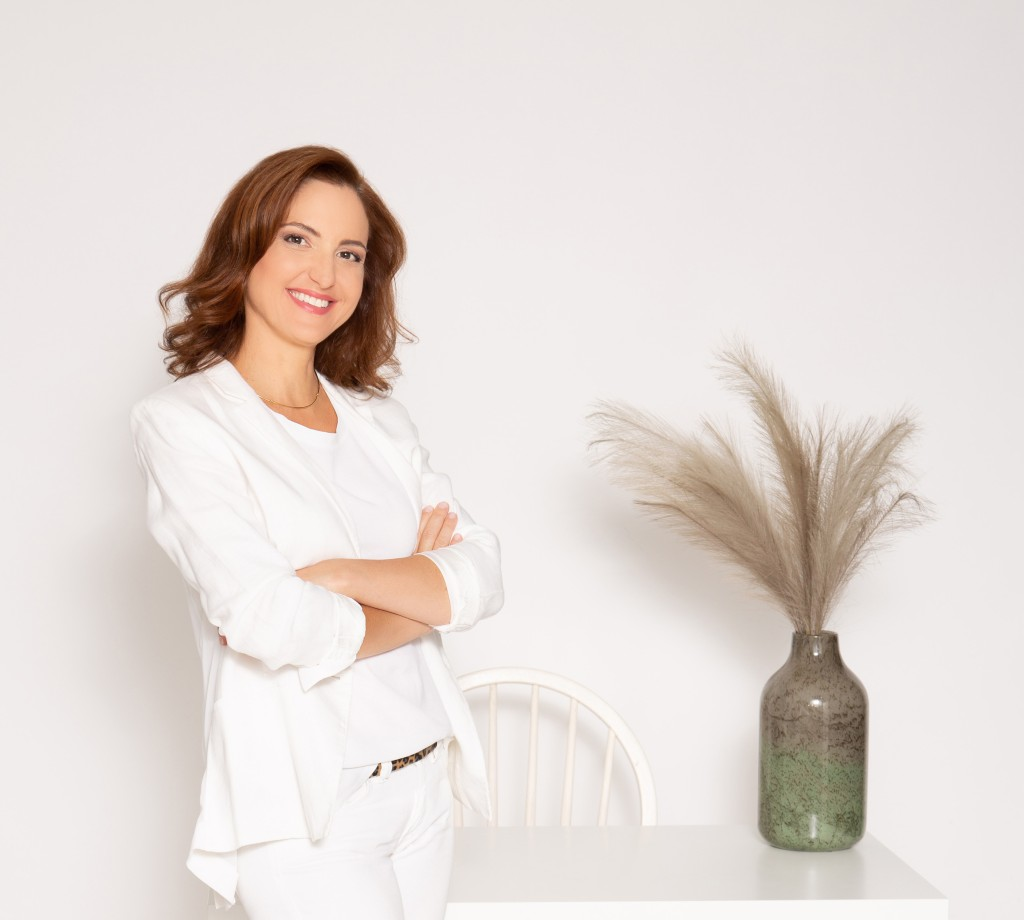 Evgenia from EWA copywriting services in white office.